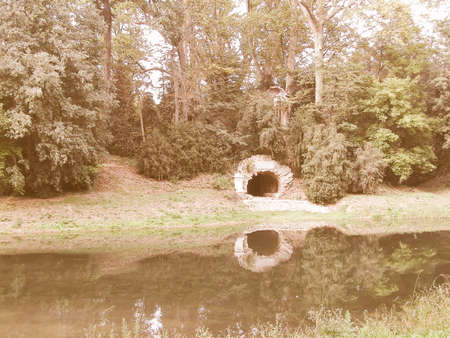 tranquillity: Vintage looking Pictoresque English garden with trees, pond, ruins of cave grotto Stock Photo