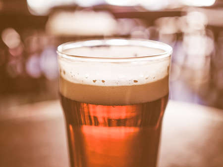 public houses: A pint of beer in a pub, focus on beer and blurred background bokeh vintage