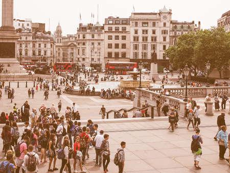 visiting: LONDON, UK - JUNE 12, 2015: Tourists visiting Trafalgar Square vintage