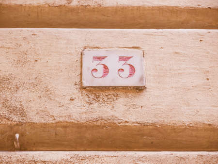 numero: A red 33 house number in Genoa where there are two series of house numbers, red and blue vintage Stock Photo