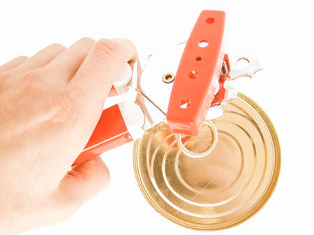 can opener: Hand opening a can with a tin can opener vintage Stock Photo