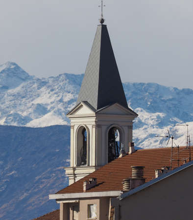 vincoli: View of the city of Settimo Torinese, Italy with steeple of St Peter in Chains church and the Alps mountains