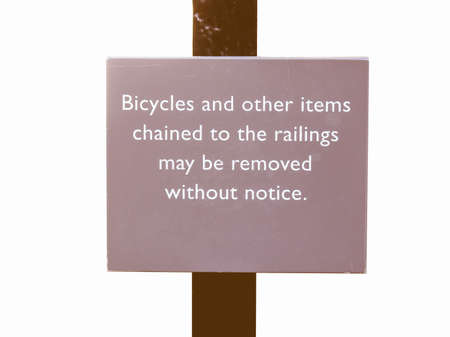 chaining: Bicycles chained to the railings may be removed without notice sign - isolated over white background vintage