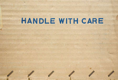 handle with care: Handle with care tag on a corrugated cardboard packet Stock Photo