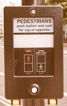 wait sign: A pedestrian crossing sign - press button and wait for signal opposite vintage Stock Photo