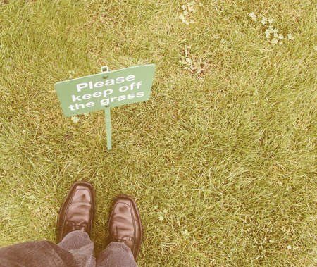 law breaking: Keep off the grass sign in a meadow, with feet breaking the law vintage Stock Photo