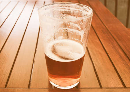 pint: Vintage looking Large glass pint of beer alcoholic drink Stock Photo