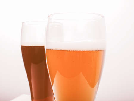 bier: Vintage looking Two glasses of German dark and white weizen beer Stock Photo