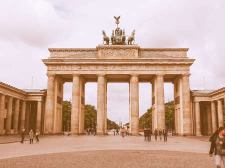 linking: BERLIN, GERMANY - MAY 11, 2014: Tourists visiting the Brandenburger Tor (Brandenburg Gate) linking East and West Berlin vintage
