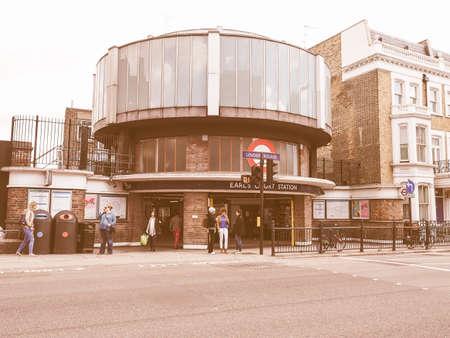 earls court: LONDON, UK - SEPTEMBER 27, 2015: Travellers at Earls Court London Underground tube station vintage