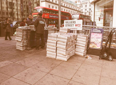 evening newspaper: LONDON, UK - JUNE 09, 2015: Distribution of the Evening Standard free newspaper on the Strand near Charing Cross station vintage