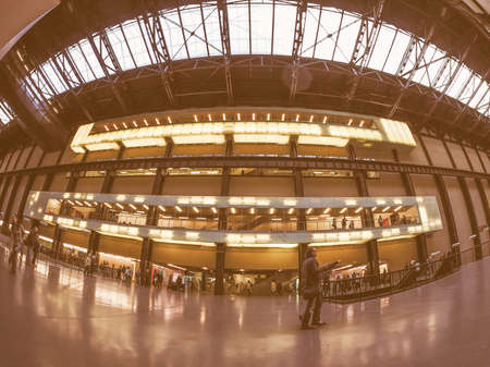 housed: LONDON, UK - SEPTEMBER 28, 2015: The Turbine Hall once housed the electricity generators of the power station now a public space part of Tate Modern art gallery in South Bank seen with fisheye lens vintage