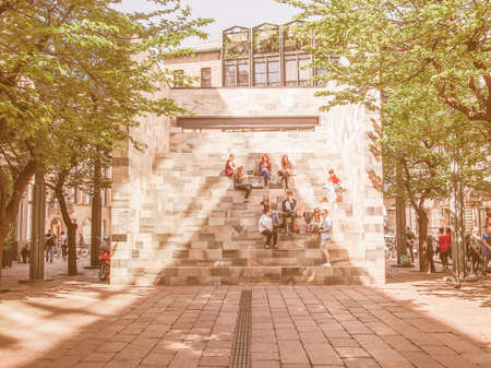 dedicated: MILAN, ITALY - APRIL 10, 2014: People seated on the stairway of the Sandro Pertini monument in Milan dedicated to the former Italian President designed by architect Aldo Rossi in 1988 vintage