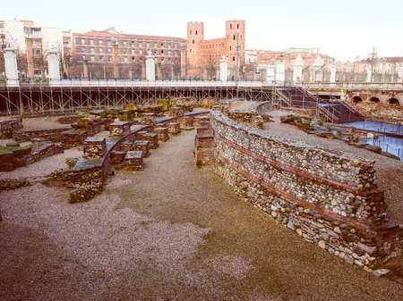teatro antiguo: Vintage looking Ruins of the ancient Roman theatre and Porte Palatine Roman city gates in Turin Italy