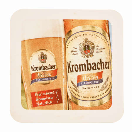 german alcohol: KREUZTAL, GERMANY - MARCH 15, 2015: Beermat of German alcohol free beer Krombacher isolated over white background vintage