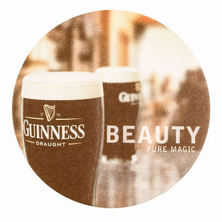 guinness beer: DUBLIN, IRELAND - MARCH 15, 2015: Beermat of Irish beer Guinness isolated over white background vintage Editorial