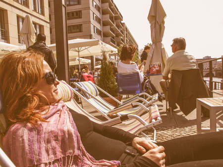 enjoing: BERLIN, GERMANY - APRIL 24: Tourists enjoing the sunny weather at bars on the River Spree bankside on April 24, 2010 in Berlin, Germany vintage Editorial