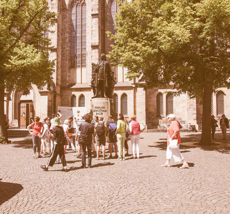st german: LEIPZIG, GERMANY - JUNE 12, 2014: People visiting the Neues Bach Denkmal new Bach monument front of the St Thomas Kirche church where Johann Sebastian Bach is buried vintage Editorial