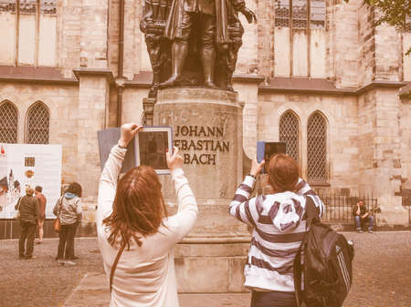 neues: LEIPZIG, GERMANY - JUNE 14, 2014: Women photographing the Neues Bach Denkmal Bach monument with a tablet pc vintage