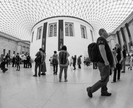 foster: LONDON, UK - SEPTEMBER 28, 2015: Tourists in the Great Court at the British Museum designed by architect Lord Norman Foster opened in year 2000 seen with fisheye lens in black and white