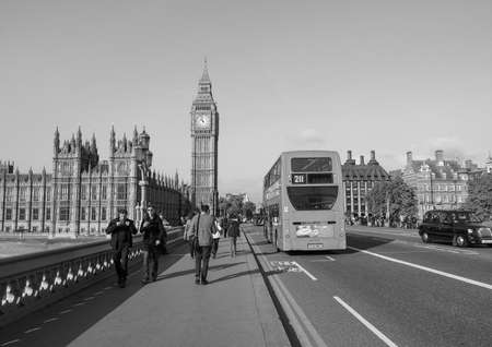 westminster bridge: LONDON, UK - SEPTEMBER 28, 2015: Tourists on Westminster Bridge at the Houses of Parliament aka Westminster Palace in black and white