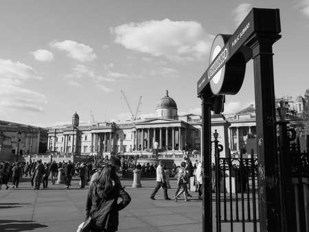 trafalgar: LONDON, UK - SEPTEMBER 27, 2015: Tourists in Trafalgar Square in black and white Editorial