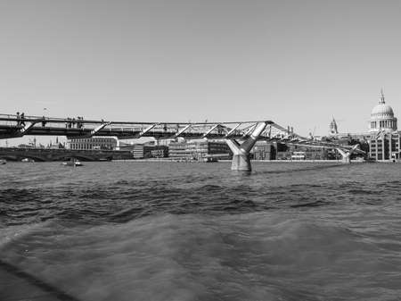 millennium bridge: LONDON, UK - SEPTEMBER 28, 2015: People crossing the Millennium Bridge over River Thames linking the City of London with the South Bank between St Paul Cathedral and Tate Modern art gallery in black and white Editorial