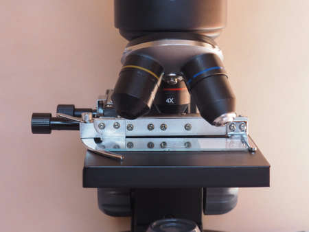 microscope lens: Detail of optical microscope lens and cross table with slide - selective focus Stock Photo