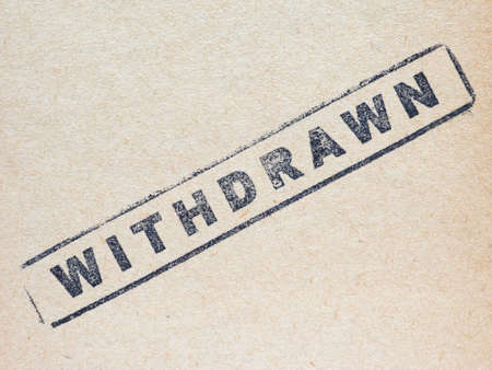 withdrawn: Black withdrawn stamp on a document on brown paper