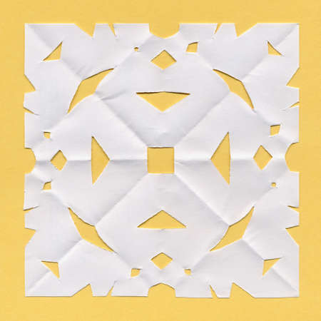 doily: Square white paper ornamental doily mat on yellow background Stock Photo