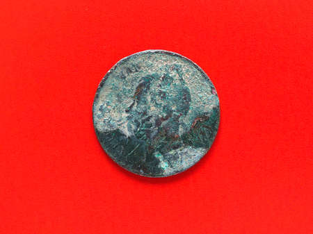 unrecognisable: Unrecognisable ancient rusted coin over red background