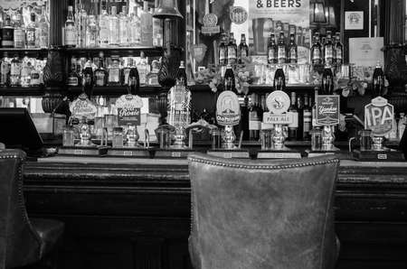 draught: LONDON, UK - SEPTEMBER 28, 2015: Draught cask beers in a traditional English Pub in black and white Editorial