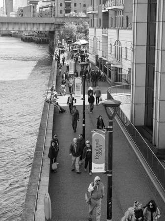 southbank: LONDON, UK - SEPTEMBER 29, 2015: Tourists walking on the River Thames South Bank in black and white