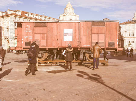 levi: TURIN, ITALY - JANUARY 23, 2015: People visiting an holocaust train for deportation of Jews to concentration forced labour and extermination camps to mark the Primo Levi exhibition in Piazza Castello vintage Editorial