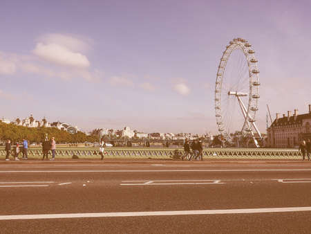millennium wheel: LONDON, UK - SEPTEMBER 28, 2015: The London Eye ferris wheel on the South Bank of River Thames aka Millennium Wheel seen from Westminster Bridge vintage