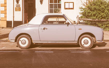 resembling: STRATFORD UPON AVON, UK - SEPTEMBER 26, 2015: Figaro is a small retro car manufactured by Nissan resembling the aesthetics of the sixties cars vintage