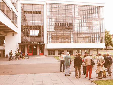 guided: DESSAU, GERMANY - JUNE 13, 2014: Visitors on an official guided tour of the Bauhaus building vintage