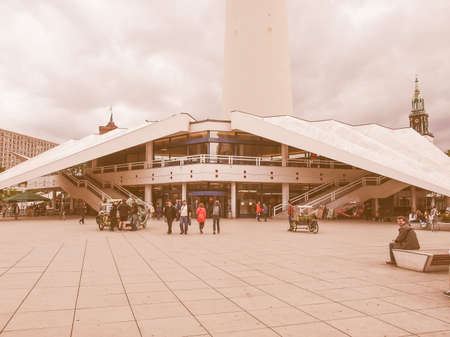 platz: BERLIN, GERMANY - MAY 08, 2014: Turists visiting Alexander Platz, the central square in East Berlin, which was designed by German architect Peter Behrens vintage