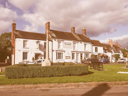 arden: TANWORTH IN ARDEN, UK - SEPTEMBER 25, 2015: The Village Green with The Bell pub and war memorial vintage