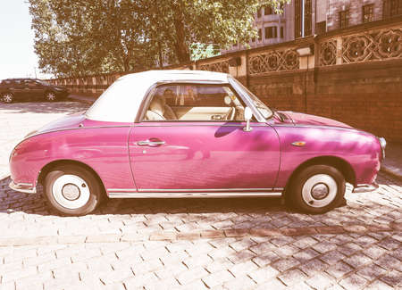 sixties: LONDON, UK - SEPTEMBER 28, 2015: Figaro is a small retro car manufactured by Nissan resembling the aesthetics of the sixties cars vintage