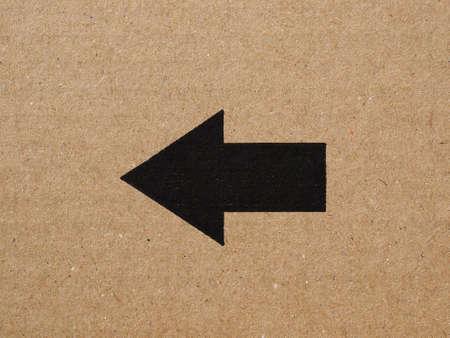 corrugated cardboard: Black arrow on brown corrugated cardboard, left direction