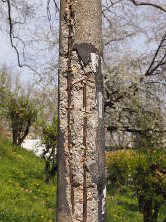 exposed concrete: Damaged concrete pole with exposed steel reinforcement resistance bars Stock Photo