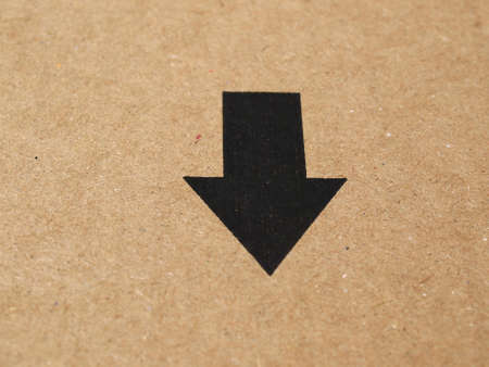 black arrow: Black arrow on brown corrugated cardboard, pointing down or towards