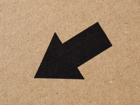 corrugated cardboard: Black arrow on brown corrugated cardboard, down left direction