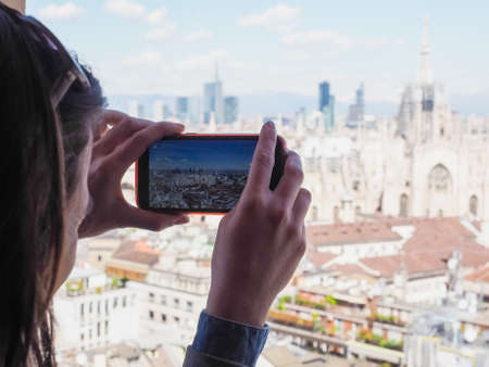 arial views: Girl photographing arial view of the skyline of the city of Milan, Italy with a smartphone