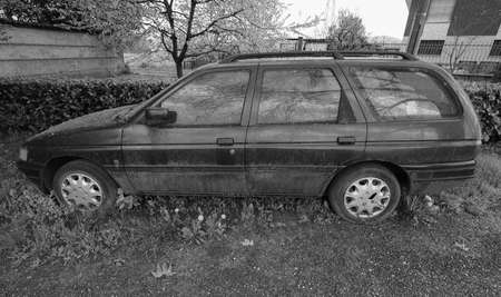 dumped: An old unused abandoned vehicle aka dumped car in black and white