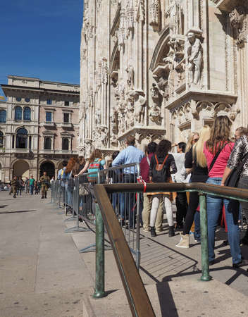 queueing: MILAN, ITALY - CIRCA APRIL 2016: Tourists queueing to visit Duomo di Milano (meaning Milan Cathedral) gothic church
