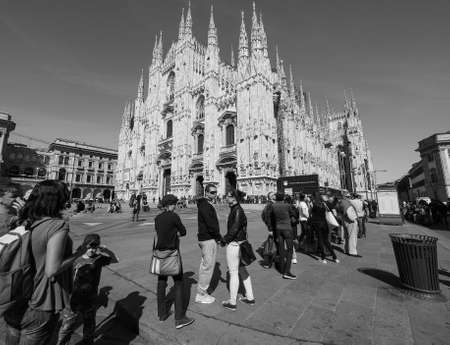 queueing: MILAN, ITALY - CIRCA APRIL 2016: Tourists queueing to visit Duomo di Milano (meaning Milan Cathedral) gothic church in black and white