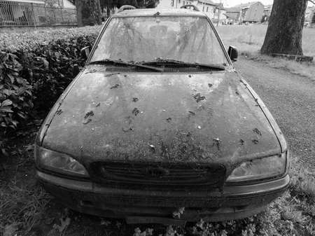 abandoned car: An old unused abandoned vehicle aka dumped car in black and white