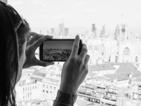 arial views: Girl photographing arial view of the skyline of the city of Milan, Italy with a smartphone in black and white